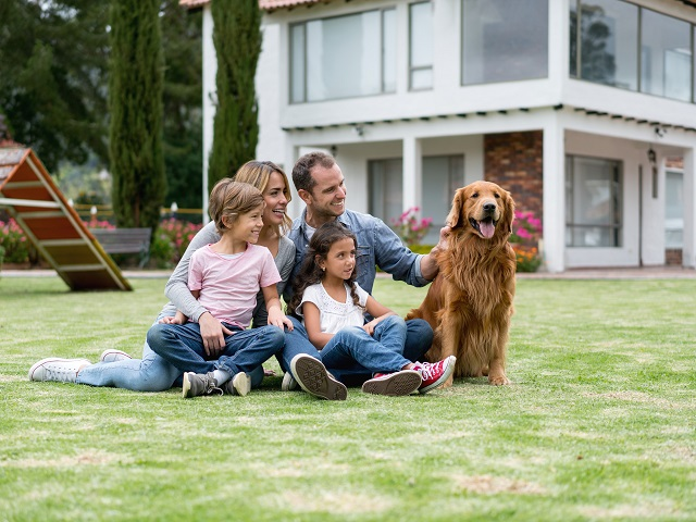 Latin American family at the park playing with their dog and looking very happy - lifestyle concepts